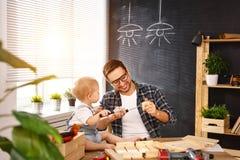 Πατέρας και γιος που χαράζονται του ξύλου στο εργαστήριο ξυλουργικής στοκ εικόνες με δικαίωμα ελεύθερης χρήσης