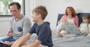 Πατέρας και γιος που χρησιμοποιούν την ψηφιακή συνεδρίαση ταμπλετών στο κρεβάτι πέρα από τη μητέρα με την οικογένεια φορητών προσ απόθεμα βίντεο