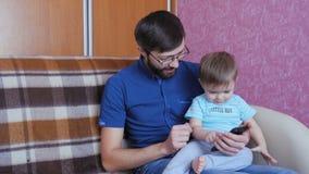 Πατέρας και γιος που χρησιμοποιούν το έξυπνο τηλέφωνο από κοινού απόθεμα βίντεο