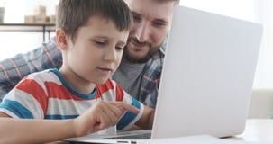 Πατέρας και γιος που χρησιμοποιούν το lap-top στο σπίτι απόθεμα βίντεο