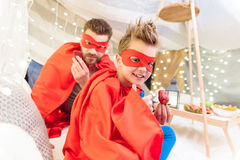 Πατέρας και γιος στα κοστούμια superhero που τρώνε τις φράουλες στο γενικό οχυρό Στοκ Εικόνες