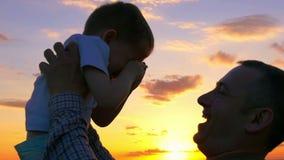 Πατέρας και γιος στο ηλιοβασίλεμα Ο μπαμπάς κρατά το γιο του στα όπλα του, φιλιά απόθεμα βίντεο