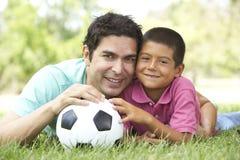 Πατέρας και γιος στο πάρκο με το ποδόσφαιρο Στοκ φωτογραφία με δικαίωμα ελεύθερης χρήσης