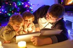 Πατέρας και δύο μικρά αγόρια μικρών παιδιών που διαβάζουν το βιβλίο από την καπνοδόχο, τα κεριά και την εστία Στοκ φωτογραφία με δικαίωμα ελεύθερης χρήσης