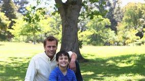 Πατέρας και η συνεδρίαση παιδιών του σε ένα πάρκο απόθεμα βίντεο