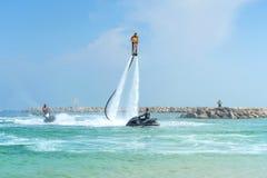 Πατέρας και η τοποθέτηση κορών του στο νέο flyboard στο καραϊβικό trop Στοκ Εικόνα