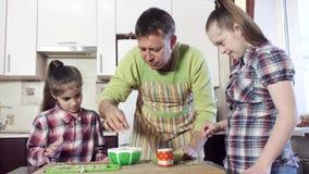 Πατέρας και κόρες στην κουζίνα που προετοιμάζει την πράσινη σαλάτα απόθεμα βίντεο