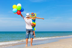 Πατέρας και κόρη με τα μπαλόνια που παίζουν στην παραλία Στοκ Εικόνες