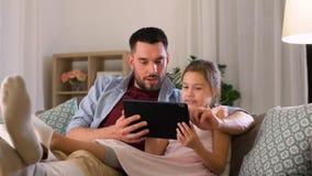 Πατέρας και κόρη με το PC ταμπλετών στο σπίτι απόθεμα βίντεο