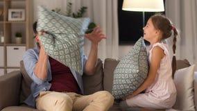 Πατέρας και κόρη που έχουν την πάλη μαξιλαριών στο σπίτι απόθεμα βίντεο