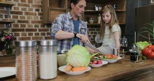 Πατέρας και κόρη που αλατίζουν τα λαχανικά που μαγειρεύουν τα τρόφιμα μαζί ενώ η μητέρα και ο γιος χρησιμοποιούν τη συνεδρίαση υπ απόθεμα βίντεο