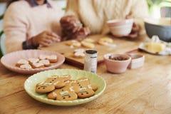 Πατέρας και κόρη που διακοσμούν τα μπισκότα στο σπίτι από κοινού Στοκ Φωτογραφίες