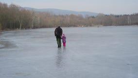 Πατέρας και κόρη που μαθαίνουν στο σαλάχι πάγου στον παγωμένο πάγο λιμνών φιλμ μικρού μήκους