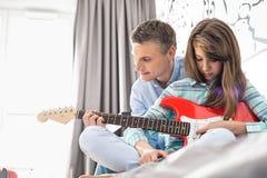 Πατέρας και κόρη που παίζουν την ηλεκτρική κιθάρα στο σπίτι στοκ εικόνες