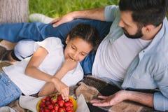 Πατέρας και κόρη που τρώνε τις φράουλες στηργμένος στο καρό στο πικ-νίκ Στοκ φωτογραφία με δικαίωμα ελεύθερης χρήσης