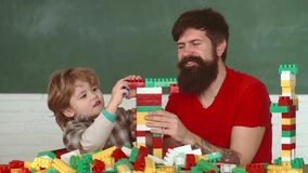 Πατέρας και λίγος γιος με το τρυπάνι που διατρυπά την ξύλινη σανίδα στο εργαστήριο Οικοδόμοι παιχνιδιού αγοριών και πατέρων παιδι φιλμ μικρού μήκους
