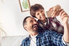 Πατέρας και λίγος γιος που κάθονται στο σπίτι στον καναπέ που παίρνει selfie στο smartphone που φαίνεται εύθυμη κινηματογράφηση σ στοκ εικόνες