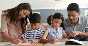 Πατέρας και μητέρα που βοηθούν τα παιδιά με την εργασία φιλμ μικρού μήκους