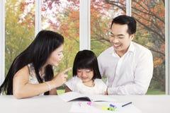 Πατέρας και μητέρα που συμβουλεύουν το παιδί τους για να μάθει στοκ εικόνες