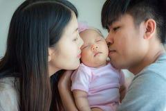 Πατέρας και μητέρα που φιλούν ένα μικρό μωρό, πατρότητα, οικογένεια συμπυκνωμένη στοκ φωτογραφίες με δικαίωμα ελεύθερης χρήσης