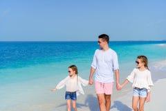 Πατέρας και μικρά κορίτσια που περπατούν στην άσπρη αμμώδη παραλία Στοκ Εικόνες
