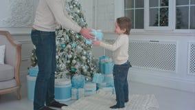 Πατέρας και ο ευτυχής γιος του που επιλέγουν τα χριστουγεννιάτικα δώρα που ανοίγουν Στοκ εικόνα με δικαίωμα ελεύθερης χρήσης