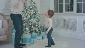 Πατέρας και ο ευτυχής γιος του που επιλέγουν τα χριστουγεννιάτικα δώρα που ανοίγουν φιλμ μικρού μήκους
