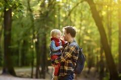 Πατέρας και ο μικρός γιος του κατά τη διάρκεια των δραστηριοτήτων πεζοπορίας στο δάσος στο ηλιοβασίλεμα Στοκ Εικόνες
