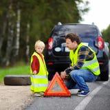 Πατέρας και ο μικρός γιος του που επισκευάζουν το αυτοκίνητο και που αλλάζουν τη ρόδα toget Στοκ Φωτογραφία