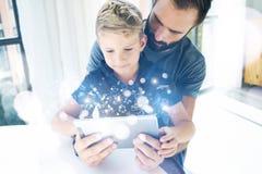 Πατέρας και ο μικρός γιος του που παίζουν μαζί στον κινητό υπολογιστή, στήριξη εσωτερική Γενειοφόρο άτομο με το νέο αγόρι που χρη Στοκ Εικόνα