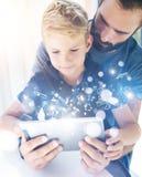 Πατέρας και ο μικρός γιος του που παίζουν μαζί στον κινητό υπολογιστή, στήριξη εσωτερική Γενειοφόρο άτομο με το νέο αγόρι που χρη Στοκ εικόνα με δικαίωμα ελεύθερης χρήσης