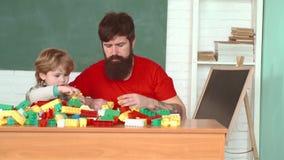 Πατέρας και παιδί που βοηθούν μαζί στο σπίτι Γιος στο σκληρό καπέλο που βοηθά τον πατέρα του Οικοδόμοι παιχνιδιού αγοριών και πατ απόθεμα βίντεο