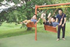 Πατέρας και παιδιά που παίζουν με την ταλάντευση Στοκ φωτογραφία με δικαίωμα ελεύθερης χρήσης