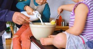 Πατέρας και παιδιά που χύνουν και που ανακατώνουν το γάλα 4k φιλμ μικρού μήκους