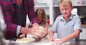 Πατέρας και παιδιά που κατασκευάζουν την πίτσα στην κουζίνα από κοινού απόθεμα βίντεο