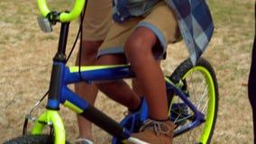 Πατέρας και παππούς που διδάσκουν το παιδί τους για να οδηγήσει το ποδήλατο απόθεμα βίντεο