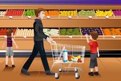 Πατέρας και τα παιδιά του που κάνουν τις αγορές παντοπωλείων ελεύθερη απεικόνιση δικαιώματος