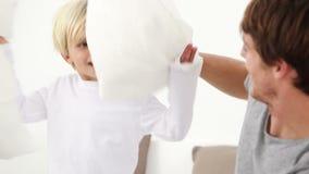 Πατέρας και το παιδί του που παίζουν με τα μαξιλάρια φιλμ μικρού μήκους