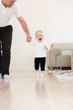 Πατέρας και το όμορφο κοριτσάκι του που παίζουν και που μαθαίνουν πώς να περπατήσει Στοκ Φωτογραφία