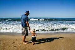 Πατέρας και 2χρονος γιος που αντιμετωπίζουν τα ωκεάνια κύματα στην παραλία από το β στοκ φωτογραφίες με δικαίωμα ελεύθερης χρήσης