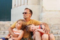 Πατέρας με δύο κουρασμένα παιδιά που στηρίζονται έξω Στοκ εικόνες με δικαίωμα ελεύθερης χρήσης