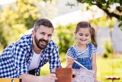Πατέρας με μια μικρή κόρη έξω, που χρωματίζει το ξύλινο birdhouse στοκ εικόνες