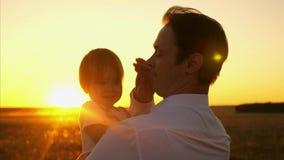 Η οικογένεια, μπαμπάς φέρνει στα όπλα του μια μικρή κόρη στο πάρκο πατέρας με μικρά παιδικά παιχνίδια στις ακτίνες ενός όμορφου η απόθεμα βίντεο