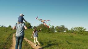 Πατέρας με τα παιδιά που προωθούν έναν ικτίνο αέρα απόθεμα βίντεο