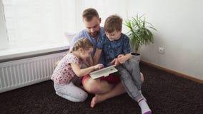 Πατέρας με τα παιδιά που χρησιμοποιούν μια ταμπλέτα απόθεμα βίντεο