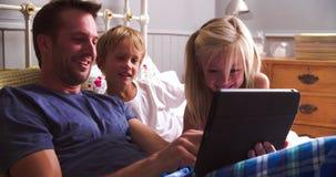 Πατέρας με τα παιδιά που εξετάζουν την ψηφιακή ταμπλέτα στο κρεβάτι απόθεμα βίντεο