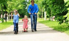 Πατέρας με τα παιδιά που οδηγούν τα μηχανικά δίκυκλα το καλοκαίρι Στοκ Φωτογραφία