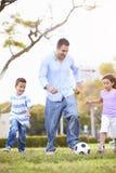 Πατέρας με τα παιδιά που παίζουν το ποδόσφαιρο στο πάρκο από κοινού Στοκ φωτογραφίες με δικαίωμα ελεύθερης χρήσης