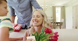 Πατέρας με τα παιδιά του που δίνουν το αιφνιδιαστικό δώρο στη σύζυγο στο καθιστικό φιλμ μικρού μήκους