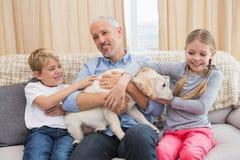 Πατέρας με τα παιδιά του στο παιχνίδι καναπέδων με το κουτάβι Στοκ φωτογραφία με δικαίωμα ελεύθερης χρήσης